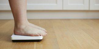 mulher na balança com sobrepeso