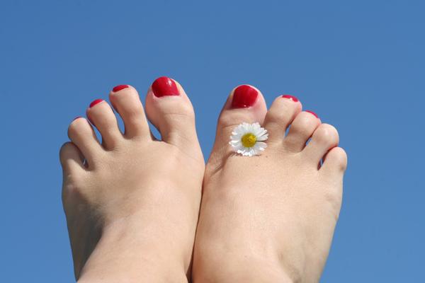 Feet against blue sky