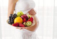 gravida com frutas na mão