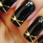unhas decoradas com fitas preto e dourado