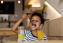 Criança bebendo suco de frutas em pó