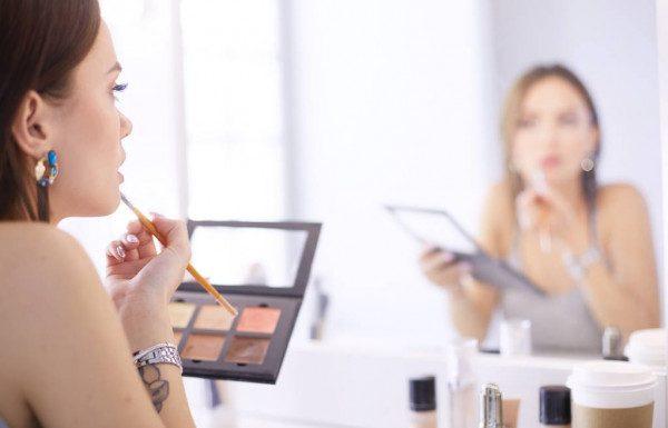 Mulher se maquiando com maquiagem vegana